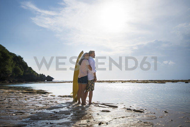 Affectionate senior couple with surfboards at beach - SBOF01041 - Steve Brookland/Westend61