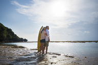 Affectionate senior couple with surfboards at beach - SBOF01041