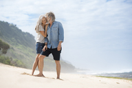 Affectionate senior couple standing on the beach - SBOF01068