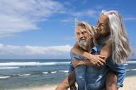Handsome senior couple having fun at the beach - SBOF01080