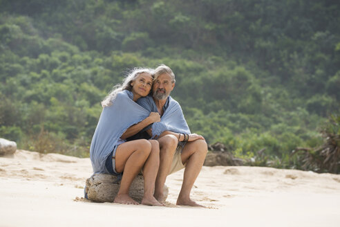 Senior couple sitting on the beach, wrapped in a blanket - SBOF01083