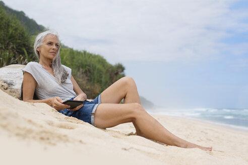Beautiful smiling senior woman lying at the beach, holding e-book - SBOF01089