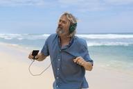 Handsome senior man with headphones dancing on the beach - SBOF01092
