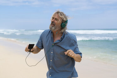 Handsome senior man with headphones dancing on the beach - SBOF01092