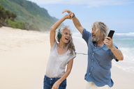 Handsome senior couple with headphones dancing on the beach - SBOF01095