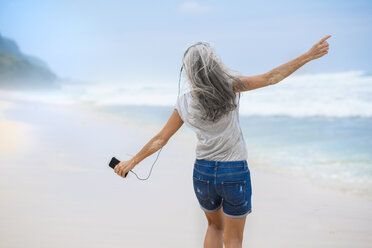 Senior woman with headphones dancing on the beach - SBOF01098