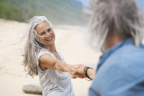 Handsome senior couple dancing on the beach - SBOF01104