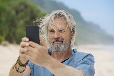 Handsome senior man taking a picture with smartphone on the beach - SBOF01107