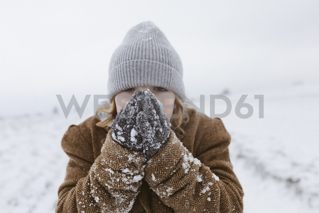 Boy in snow warming his hands - KMKF00124