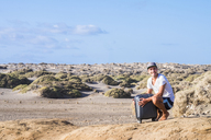 Happy man with rolling suitcase in dune landscape - SIPF01913