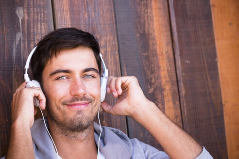 Portrait of smiling young man wearing headphones - SIPF01916