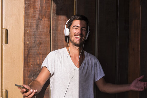 Happy young man with cell phone and headphones at wooden wall - SIPF01928