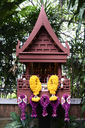 Thailand, Bangkok, Thai-style house replica as small buddhist chapel decorated with flowers - IGGF00374