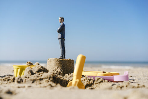 Businessman figurine standing on sand with toys around - FLAF00003