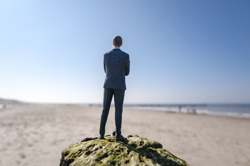 Businessman figurine standing on sand hill looking at view - FLAF00009