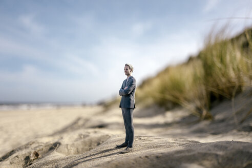 Businessman figurine standing on sand dune, looking at distance - FLAF00015