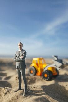 Businessman figurine standing on sand with toy digger, investment in home ownership - FLAF00018