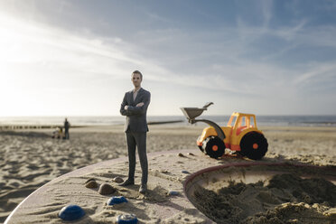 Businessman figurine standing on sand with toy digger, investment in home ownership - FLAF00021
