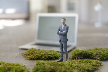 Businessman figurine with laptop standing on green moss - FLAF00024