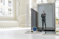 Businessman figurine standing on portable devices in a glass cage - FLAF00027