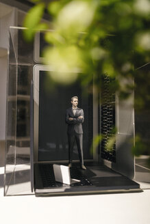 Businessman figurine standing on portable devices under a green plant - FLAF00030