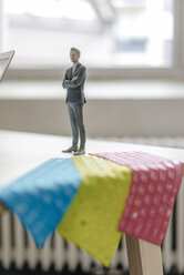 Businessnessman figurine standing on desk with tablet keyboards - FLAF00036