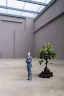 Businessman figurine standing next to a little tree - FLAF00042