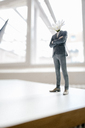 Businessman figurine with a flower head standing on desk - FLAF00048