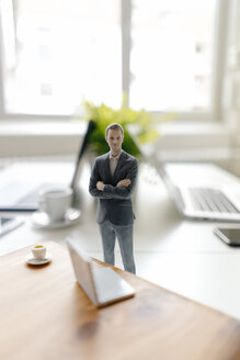 Businessman figurine standing on a desk with mobile devices and a cup of coffee - FLAF00060