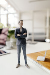 Businessman figurine standing on a desk with mobile devices - FLAF00063