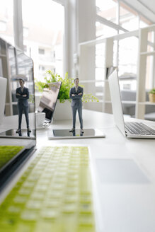 Businessman figurine standing on a desk with mobile devices - FLAF00069