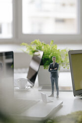 Businessman figurine standing on desk with mobile devices - FLAF00072