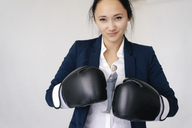 Businesswoman holding businessman figurine between boxing gloves - FLAF00075