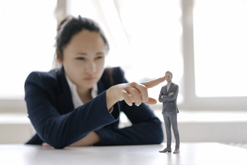 Businesswoman watching businessman figurine, standing on her desk - FLAF00078