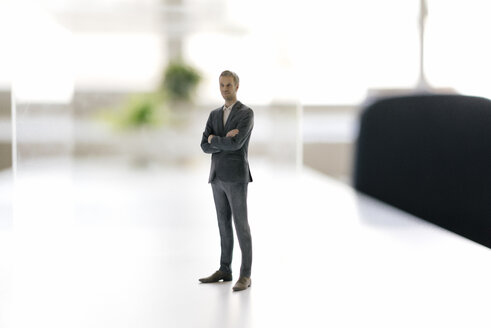 Businessman figurine standing on desk in modern office - FLAF00081