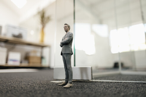 Businessman figurine standing in front of glass wall in office - FLAF00084