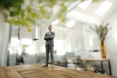 Businessman figurine standing on desk in modern office - FLAF00087