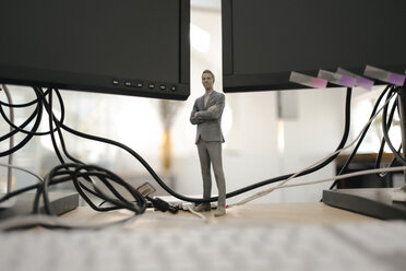 Businessman figurine standing under computer screens - FLAF00090