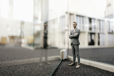 Businessman figurine standing in front of glass wall in office - FLAF00093