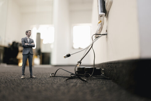 Businessman figurine standing in office, looking at disconnected cables - FLAF00096