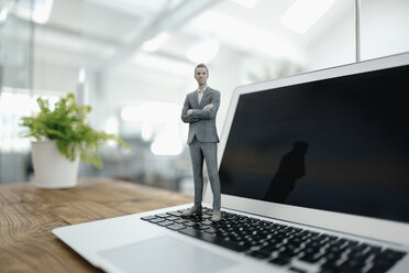 Businessman figurine standing on laptop in modern office - FLAF00099