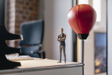 Businessman figurine standing on desk by punching ball - FLAF00105