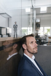 Businessman sitting in his office with his 3D portrait behind a glass pane - FLAF00108