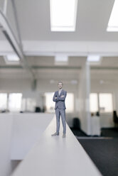 Businessman figurine standing on desk in modern office - FLAF00114