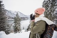 Young woman with hot drink standing in alpine winter landscape with lake - SUF00402
