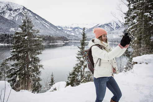 Young woman taking a selfie in alpine winter landscape with lake - SUF00405