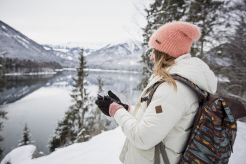 Young woman with cell phone in alpine winter landscape with lake - SUF00411