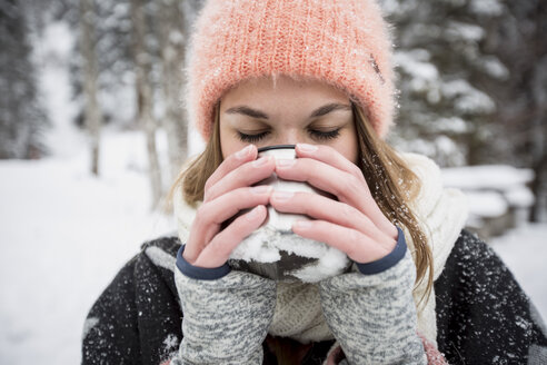 Young woman enjoying hot drink outdoors in winter - SUF00417