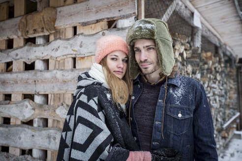 Portrait of couple in front of wood pile outdoors in winter - SUF00420