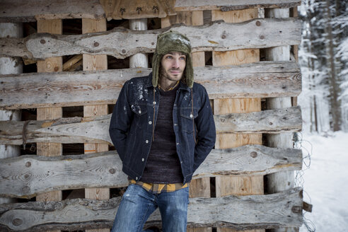 Man standing in front of wood pile outdoors in winter - SUF00423
